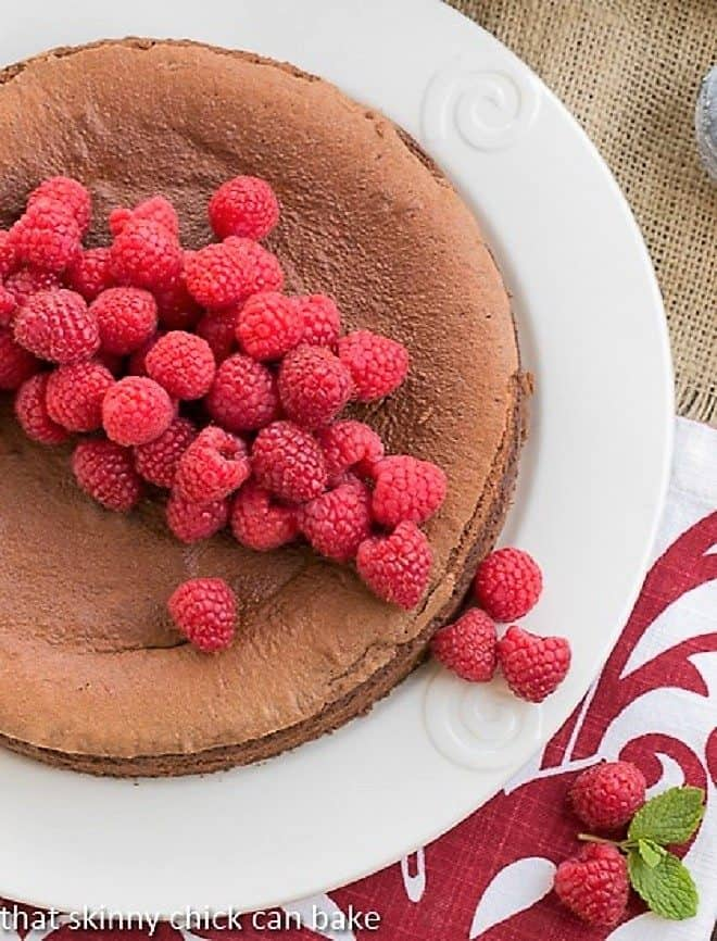 Chocolate Mousse Torte on white ceramic serving plate topped with fresh raspberries