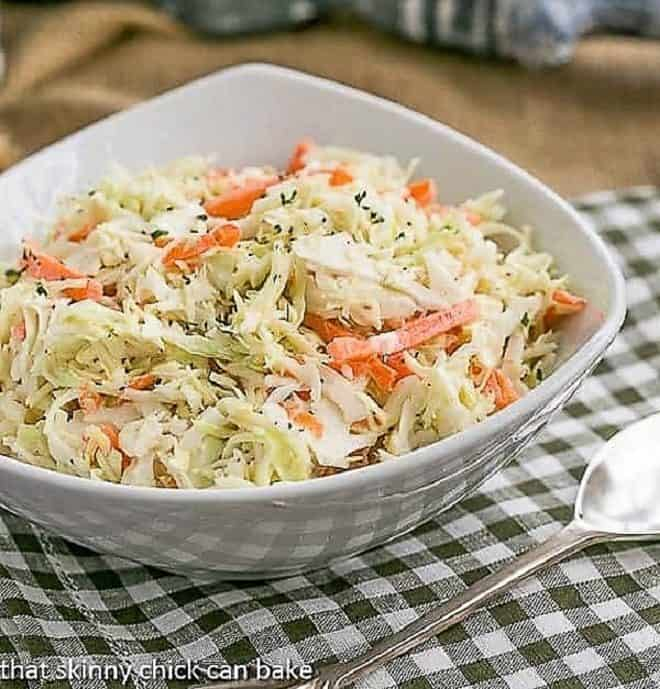 The Best Coleslaw Recipe with Buttermilk Dressing in a white bowl on a green and white checked napkin