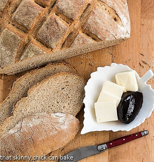 Country bread with a hearty crust sliced on a cutting board with butter and jelly