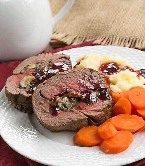 Beef Tenderloin with Gorgonzola Sauce on a white dinner plate