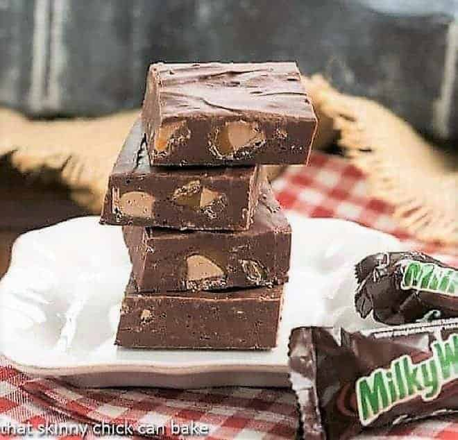 Milky Way Fudge squares stacked on a small white plate with fun-sized Milky Way bars