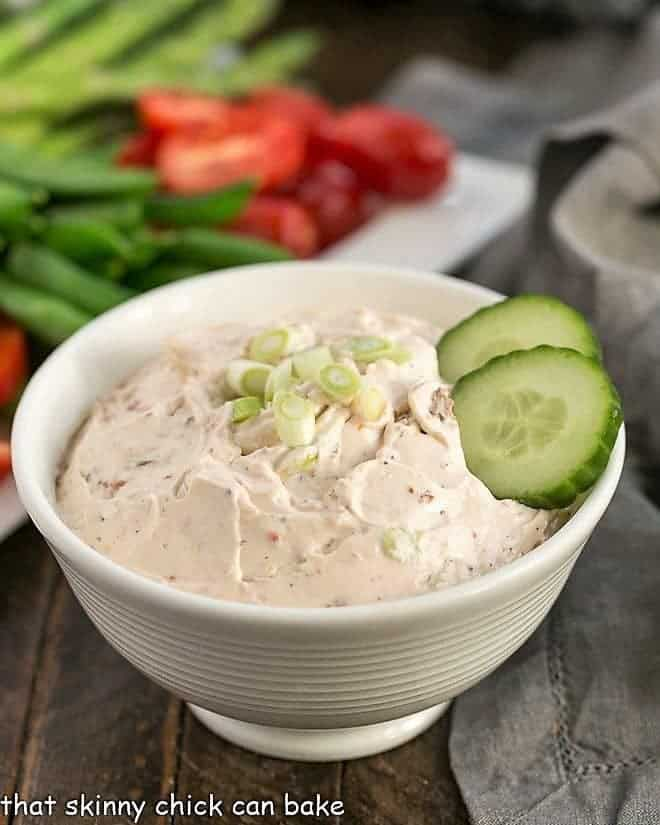 Sun-Dried Tomato Dip in a white bowl with a tray of fresh vegetables