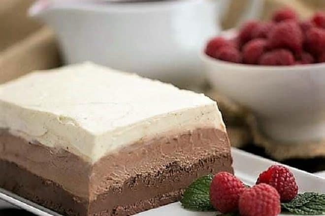 Triple Chocolate Terrine on a white platter with raspberries and mint