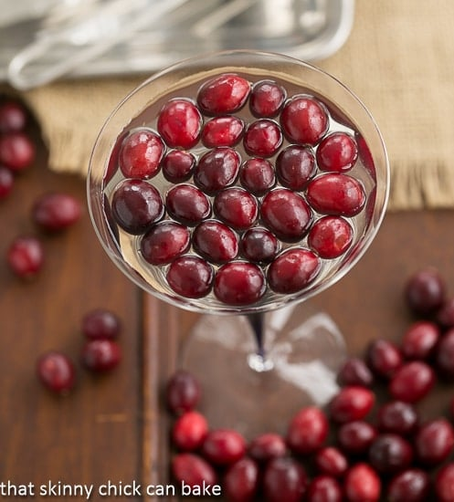 White Cosmopolitans in a martini glass topped with fresh cranberries