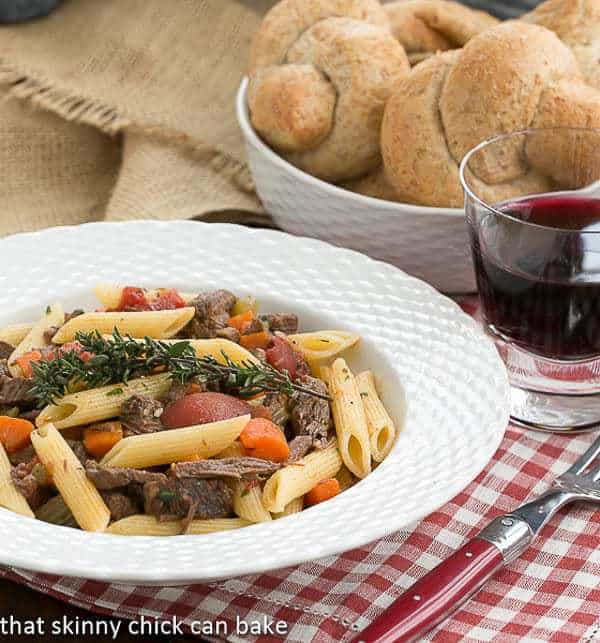Beef Burgundy Pasta served in a bowl with red wine and dinner rolls