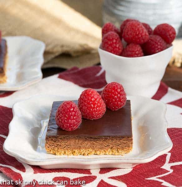 A slice of Dark Chocolate Mousse Bars on a white plate topped with raspberries