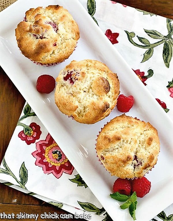 Raspberry White Chocolate Muffins on a rectangular tray with fresh raspberries and a sprig of mint
