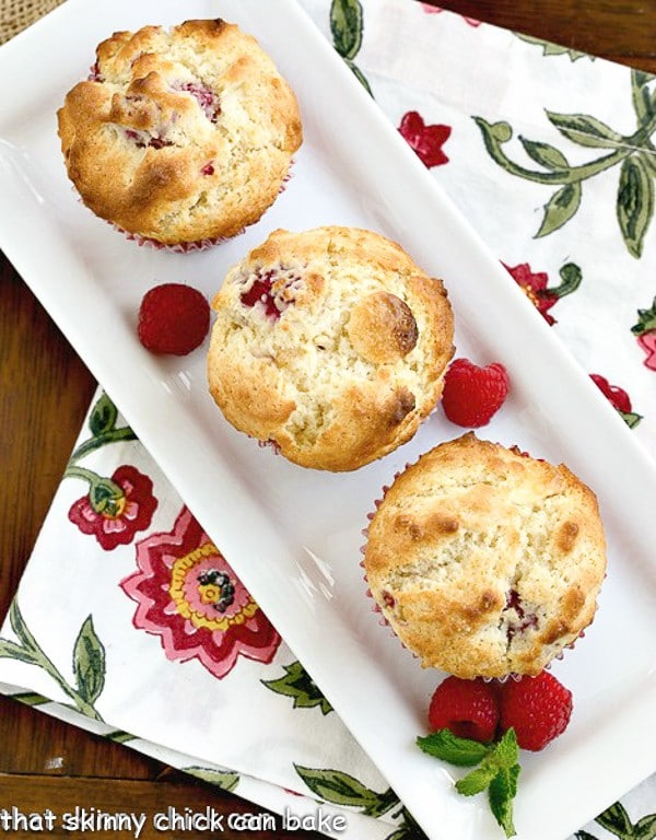 Spectacular Raspberry White Chocolate Muffins on a rectangular tray with fresh raspberries and a sprig of mint