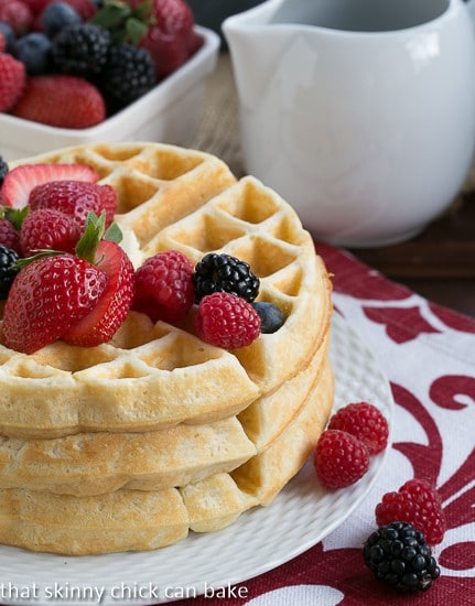 Homemade Buttermilk Waffles stacked on a white ceramic plate with a trio of berries