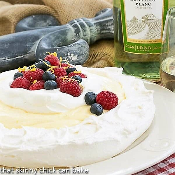 Lemon on a Cloud garnished with berries and cream on a white plate