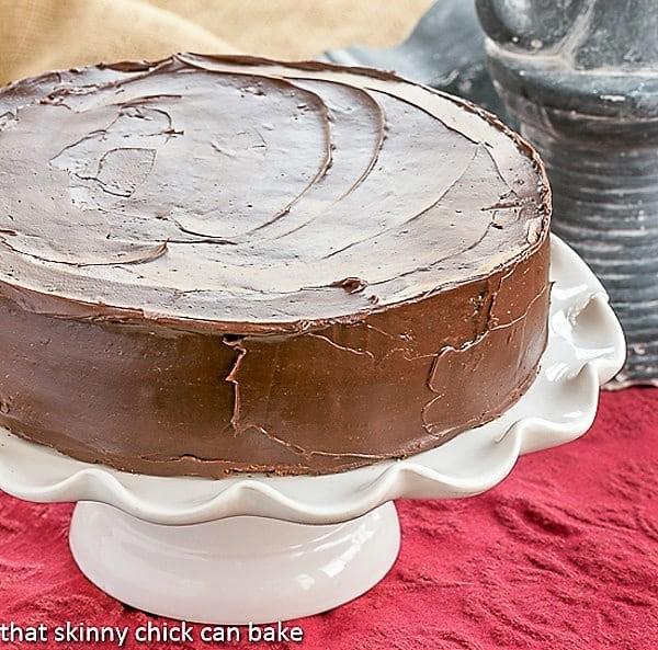 Mocha Brownie Cake on a white, ruffled cake stand