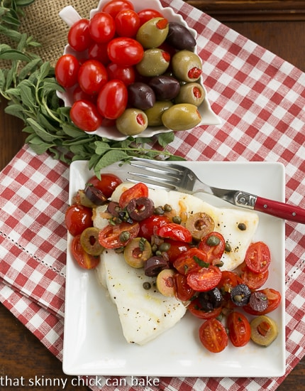 Sea Bass with Tomatoes, Olives and Capers on white plate