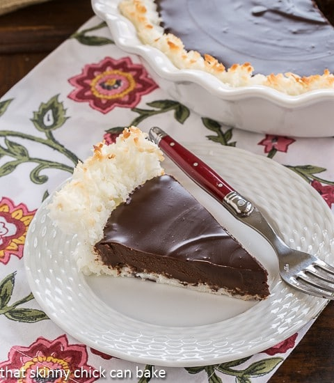 A slice of Coconut Crusted Chocolate Ganache Pie on a white plate with a red handled fork