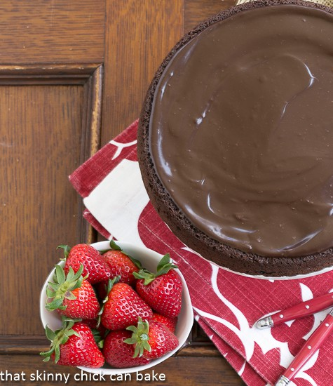 Flourless Double Chocolate Cake overhead view with a bowl of strawberries