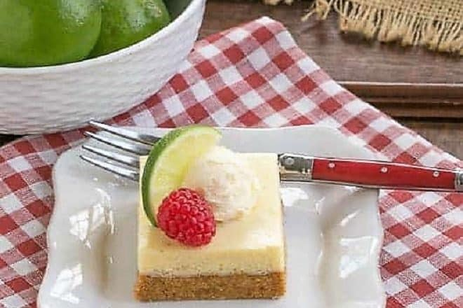 Key Lime Pie Bars on a white dessert plate over a red and white checked napkin