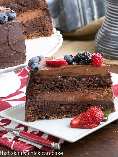 Layered Chocolate Mousse Cake slice on a white plate with berry garnish
