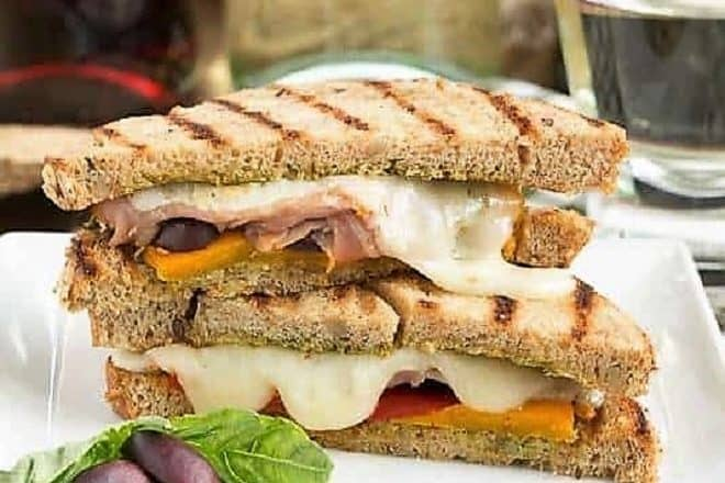 Mediterranean Grilled Cheese sliced and plated on a square white dish