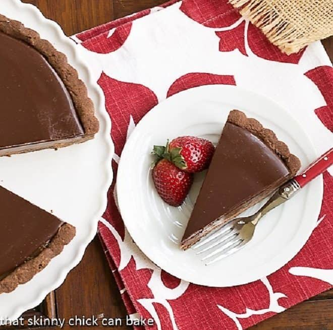 Chocolate Caramel Tart slice on a white plate with a strawberry and fork