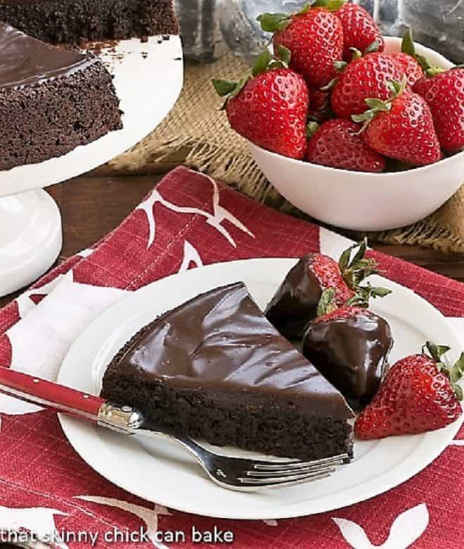 Flourless Double Chocolate Cake slice on a white plate with chocolate covered strawberries
