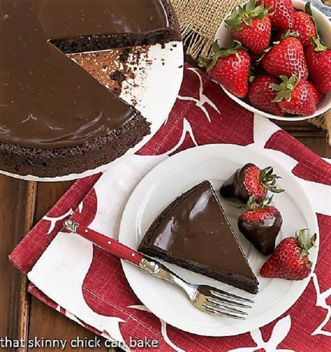 Flourless Double Chocolate Cake slice from above on a white plate with a red handled fork