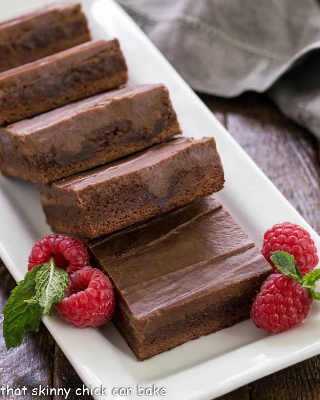 Close up of poke brownies on a white tray with fresh raspberry garnish