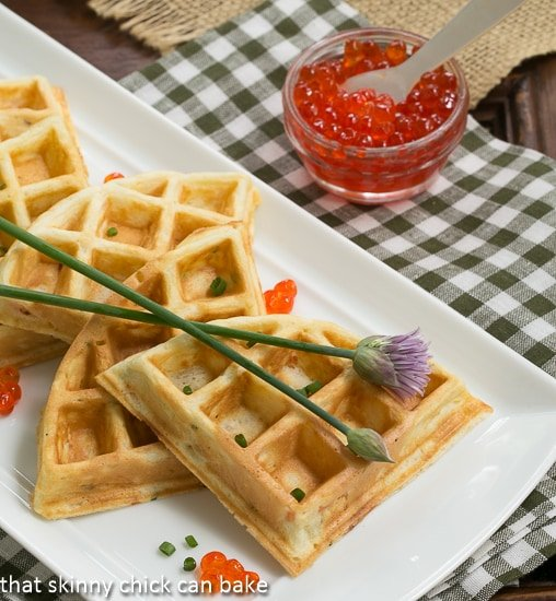 Smoked Salmon Waffles on a white platter with chives and salmon roe garnishes