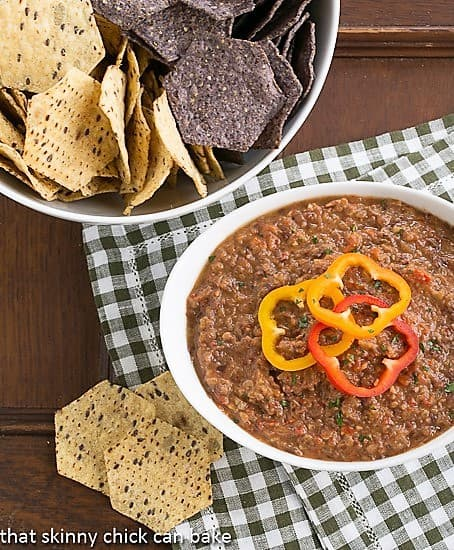 Smoky Black Bean Dip in a white bowl with a bowl of tortilla chips