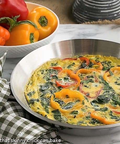 Spinach Bell Pepper Frittata in a saute pan with a bowl of bell peppers