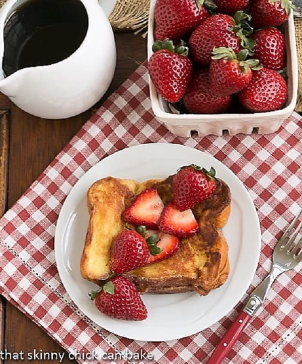 Strawberry Mascarpone Stuffed French Toast overhead view with syrup and a basket of strawberries