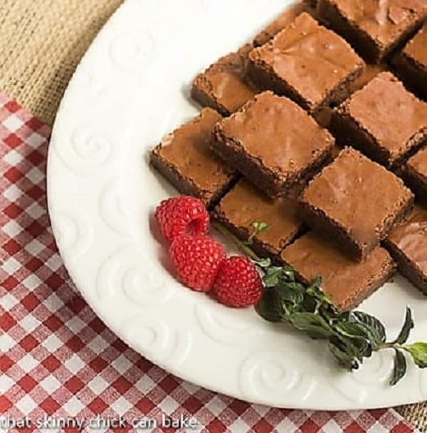 Supernatural Brownies on a oval white platter garnished with fresh raspberries and mint
