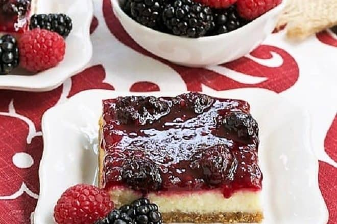 Berry Topped Cheesecake Bars sliced and served on white plates with berries