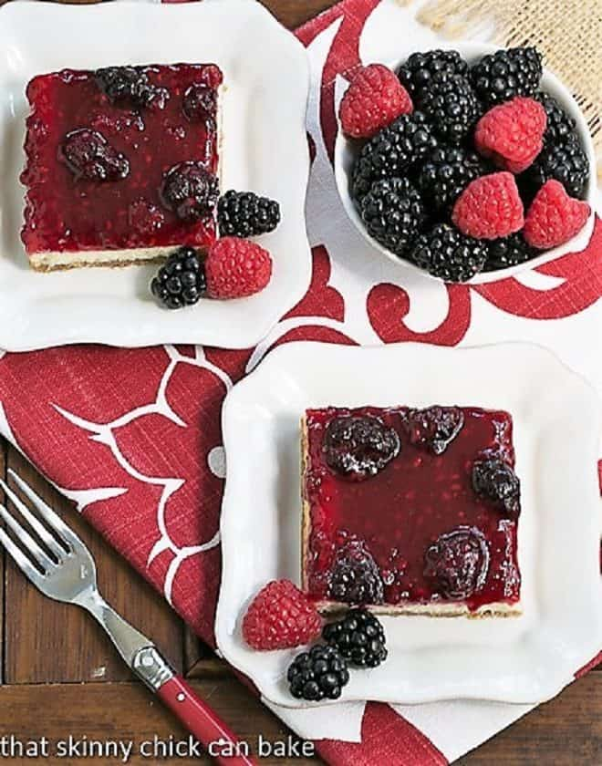 BBerry Topped Cheesecake Bars served on square white plates next to a bowl of berries