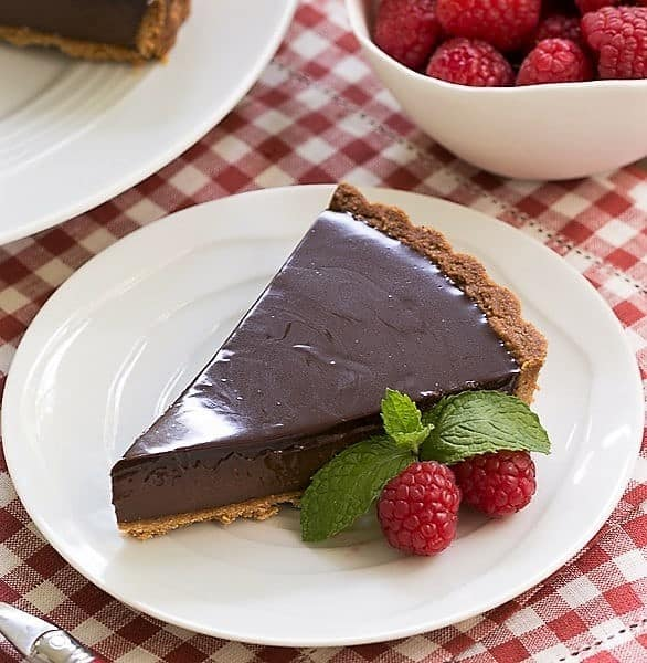 Ganache topped chocolate tart on a ceramic white plate with a raspberry garnish
