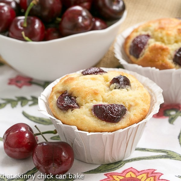 Double Cherry Muffins close up view with fresh cherries in a white bowl on a floral napkin
