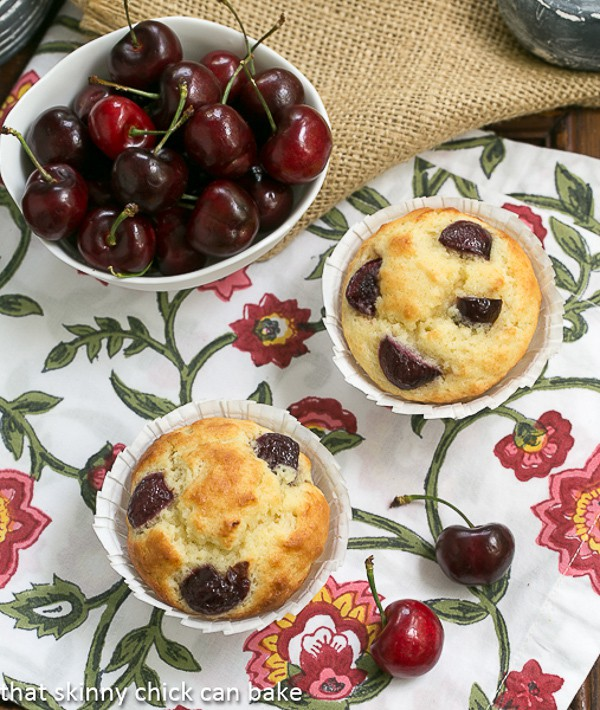 Double Cherry Muffins on a floral napkin with a bowl of dark cherries in a white bowl