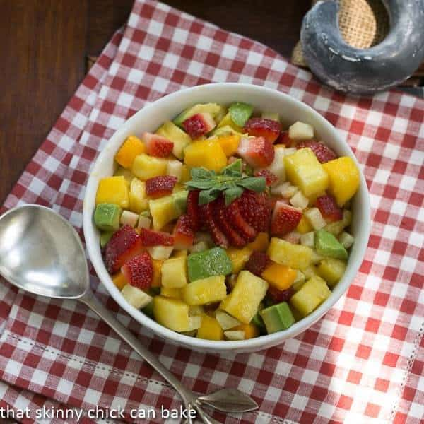 Mango Strawberry Avocado Salad in a white bowl on a red and white checked napkin