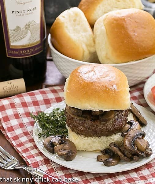 Mushroom Topped Pinot Noir Burgers on a white plate with mushrooms and herbs