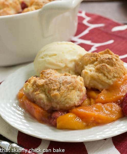 Peach Raspberry Cobbler on a white dessert plate with a scoop of vanilla ice cream