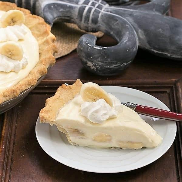 Slice of Banana Cream Cheesecake Pie on a white dessert plate