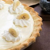 Banana Cream Cheesecake Pie close up view of pie and whipped cream and banana slice garnishes