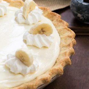Banana Cream Cheesecake Pie close up view of pie and whipped cream and banana slice garnishes