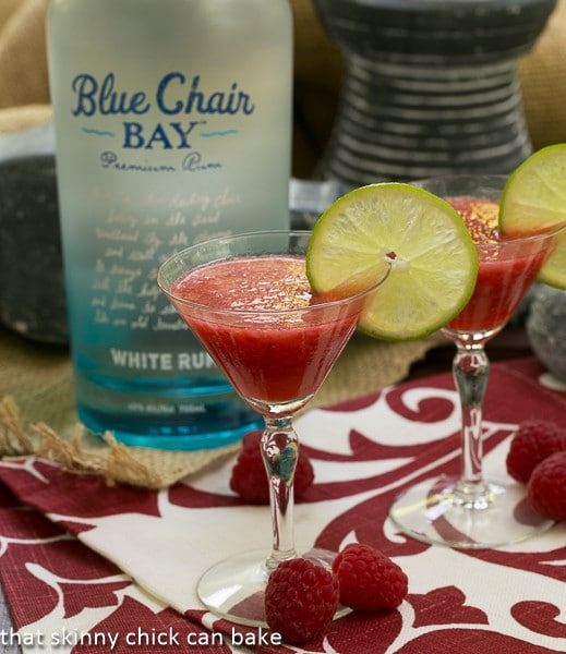 Frozen Fresh Berry Daiquiris in front of a bottle of rum