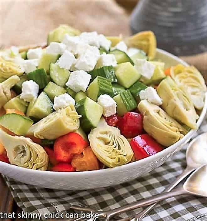 Greek Salad with Feta  in a white salad bowl with silver serving spoon and fork
