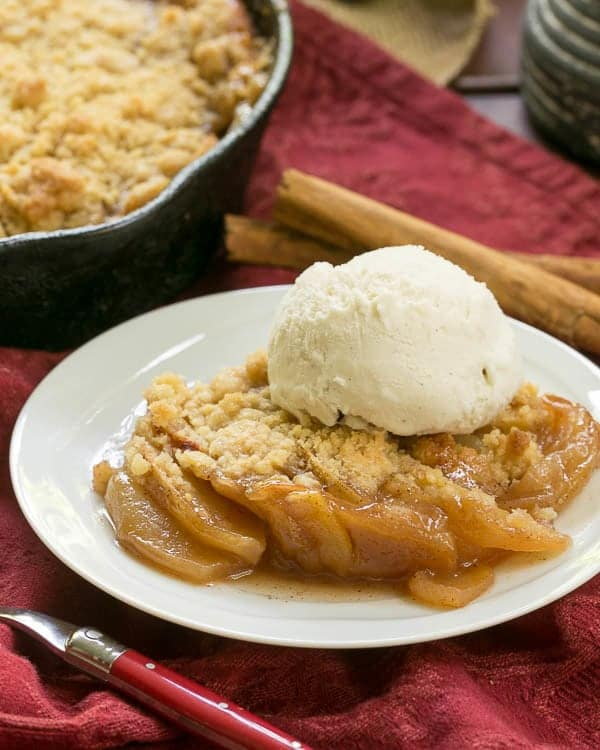 Grilled Apple Crisp topped with ice cream on a white plate