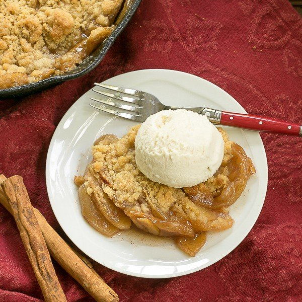 Grilled Apple Crisp on a round white plate with a scoop of vanilla ice cream