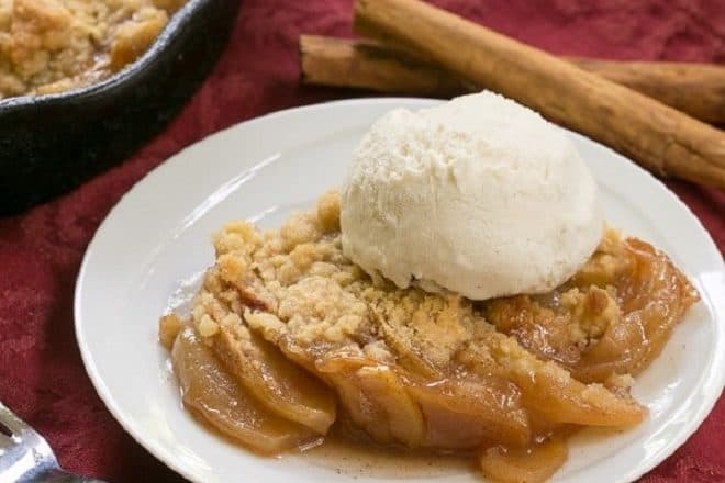 Grilled Apple Crisp topped with vanilla ice cream with a red fork and cinnamon sticks