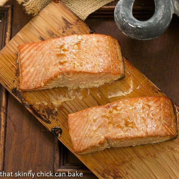 Two fillets of Grilled Cedar Plank Salmon on a cedar plank