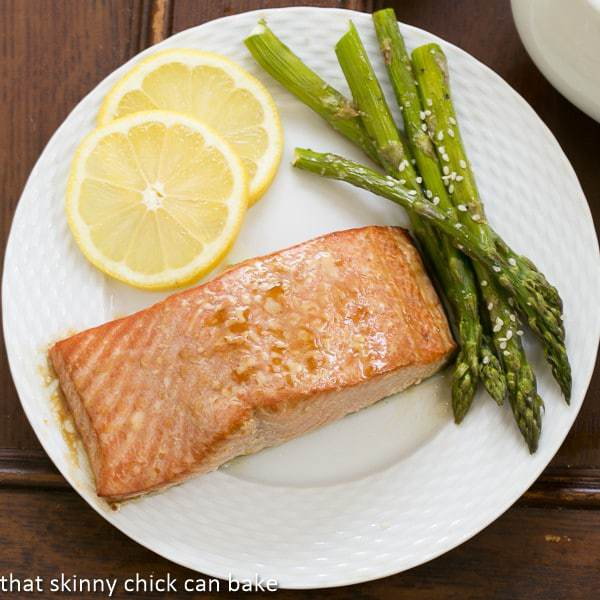 Grilled Cedar Plank Salmon on a white plate with asparagus and lemon slices