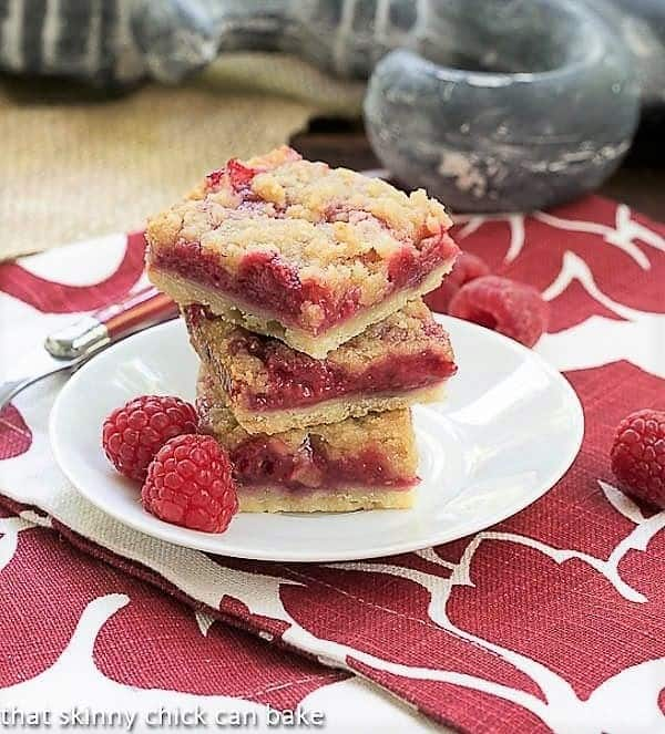 Streusel Topped Raspberry Squares stacked on a small plate with fresh raspberries