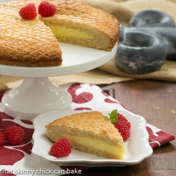 Gâteau Basque slice on a white plate garnished with raspberries